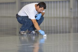 man in white shirt and jeans applying epoxy on floor